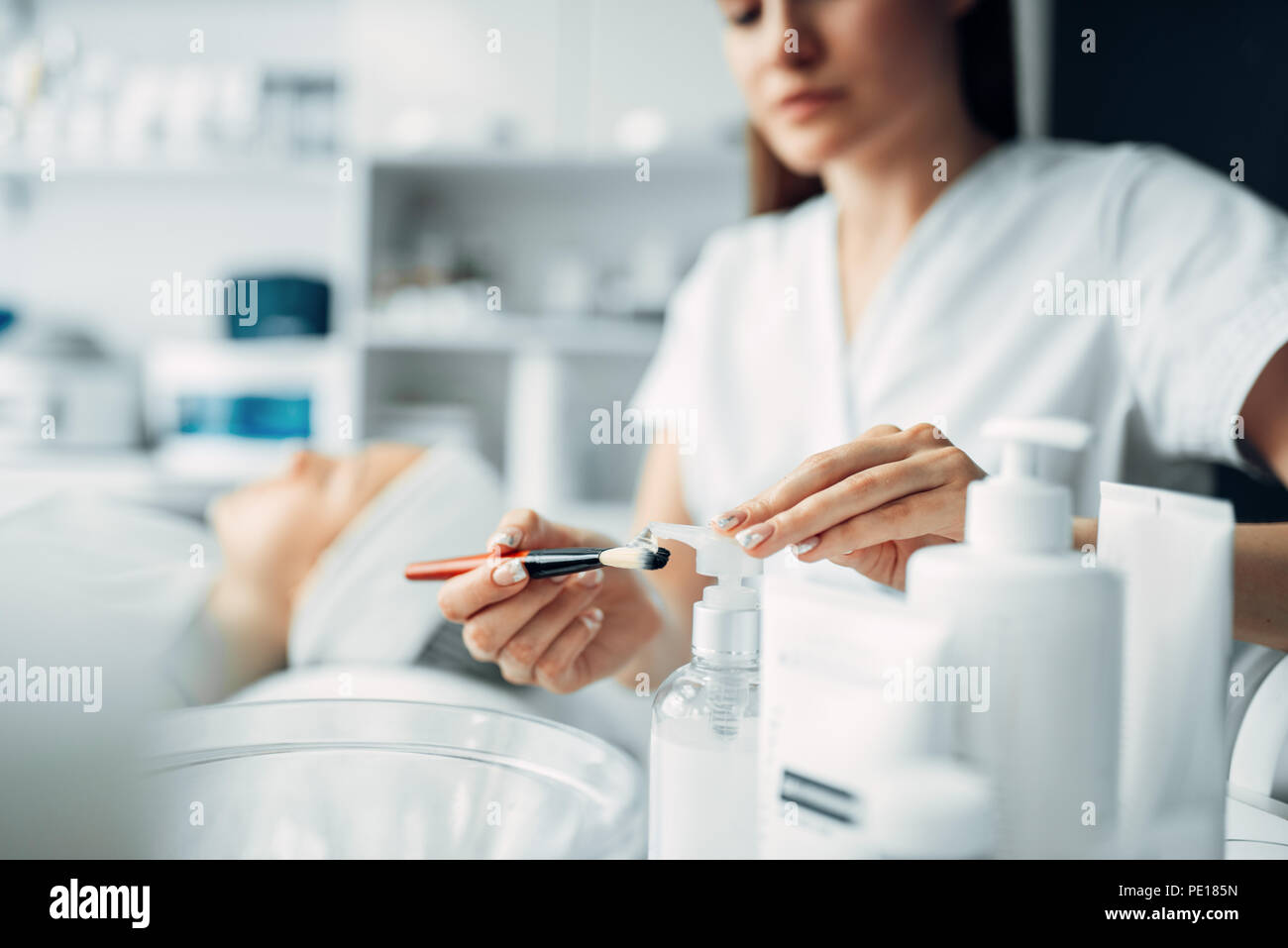 Beautician makes rejuvenation procedure to young woman, cosmetology clinic. Facial skincare in spa salon, health care - Stock Image