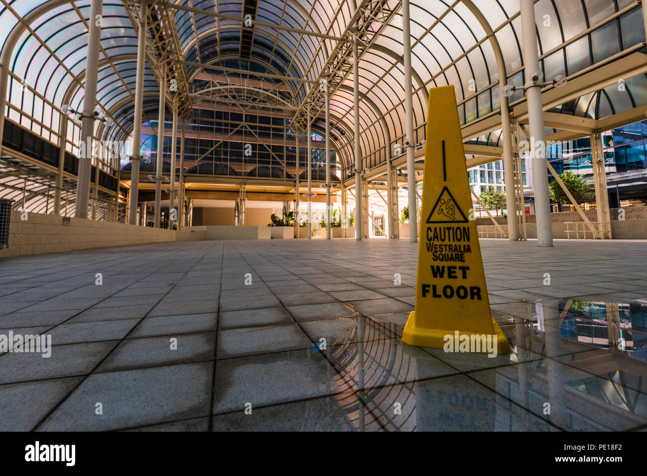 Caution Wet Floor, warning sign in an empty hall - Stock Image
