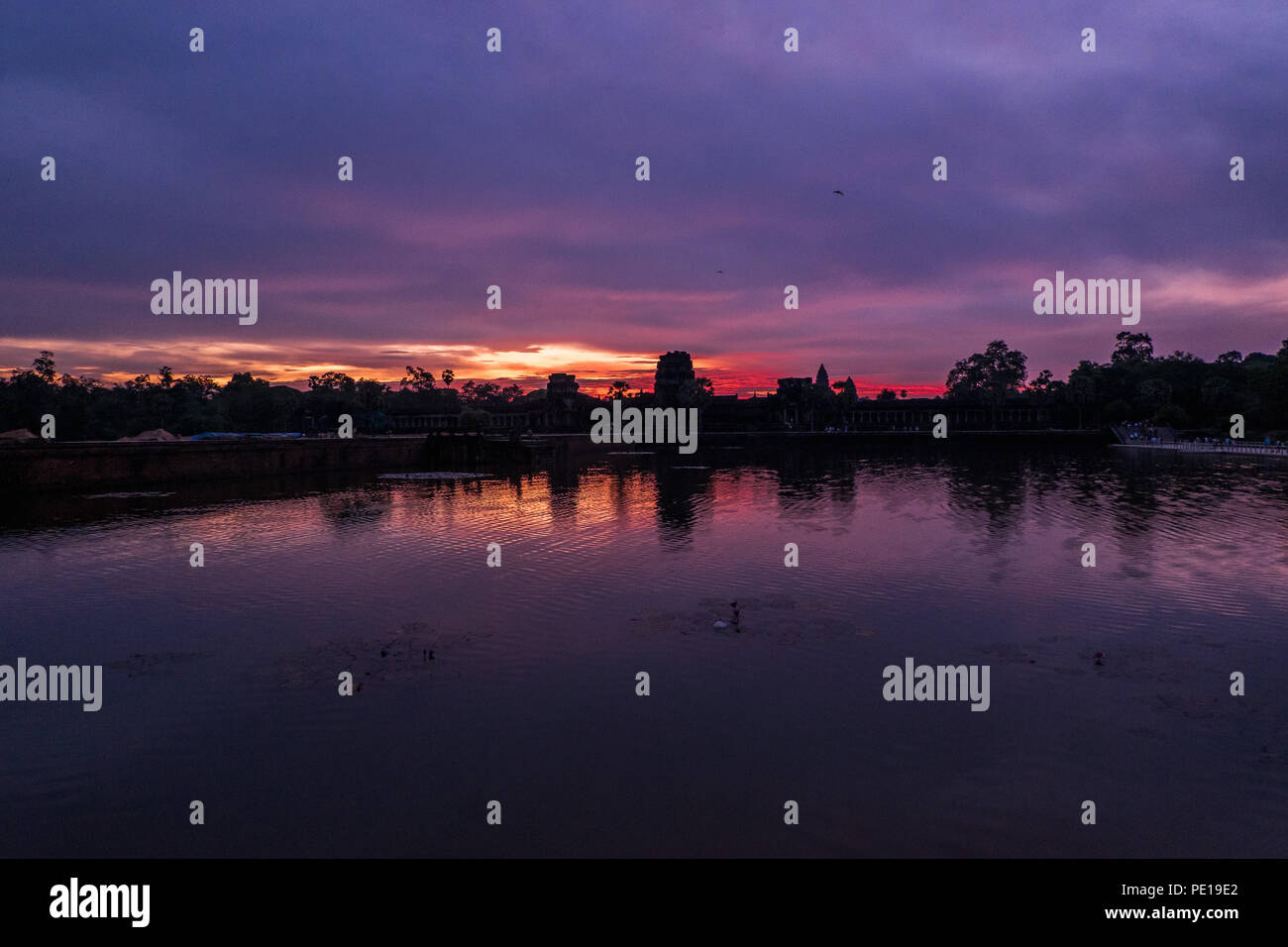 Sunrise over the moat surrounding the temple Angkor Wat - the largest religious monument in the world - near Siem Reap, Cambodia Stock Photo