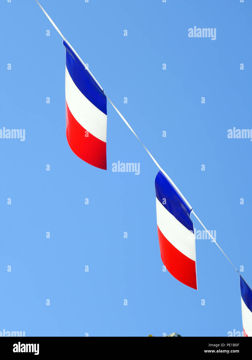 French String Flag Banners in rows floating in a summer blue sky in Cessenon-sur-Orb, France - Stock Image