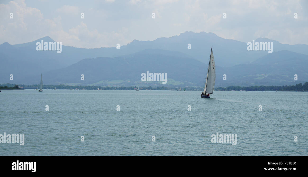 sailing boat at lake with mountains in background - Stock Image