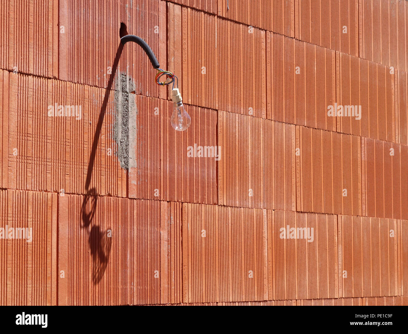 Single light bulb hanging from a wire on the exterior of a newly built wall at a house in Cessenon-sur-Orb, France - Stock Image
