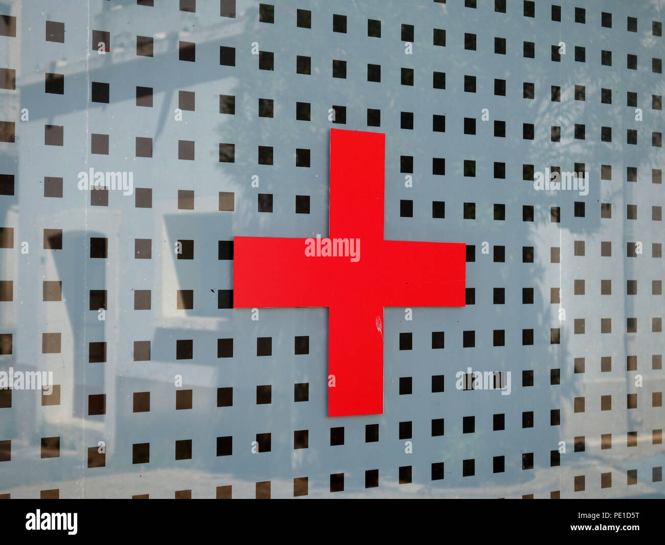 Red Cross on window of Doctors surgery and Medical office in Cessenon-sur-Orb, France - Stock Image