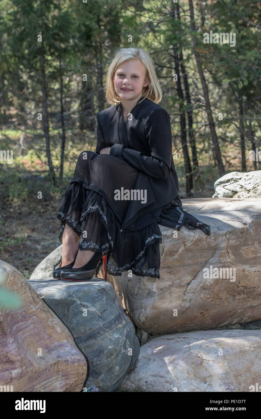 521d70fec00 Attractive young girl, blonde, fashionably dressed in black outfit,, sitting  outdoors on large rock, looking at camera.