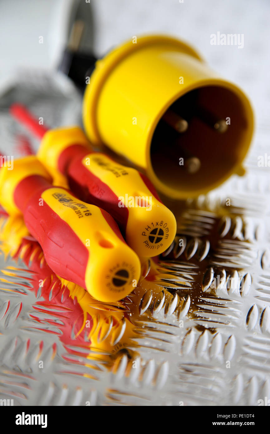 Electric screwdrivers with an industrial electric plug on a steel chequer tread plate Stock Photo