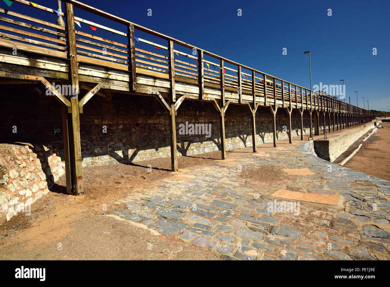 The elevated down platform at Dawlish railway station, seen from the beach below. - Stock Image