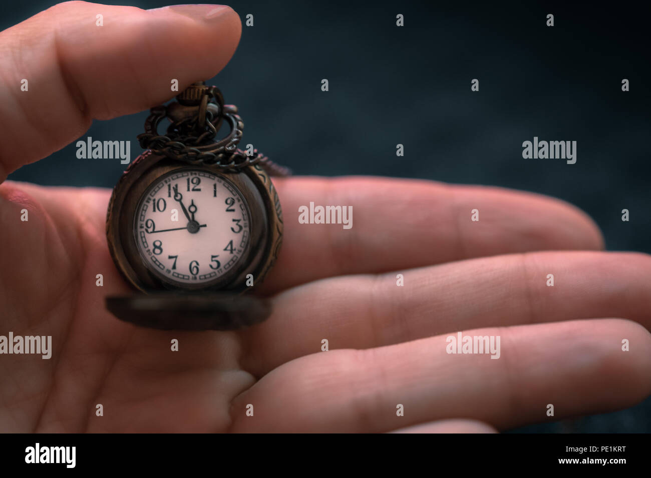 Hand holding a pocket watch with time showing as five to twelve o'clock, time concept - Stock Image