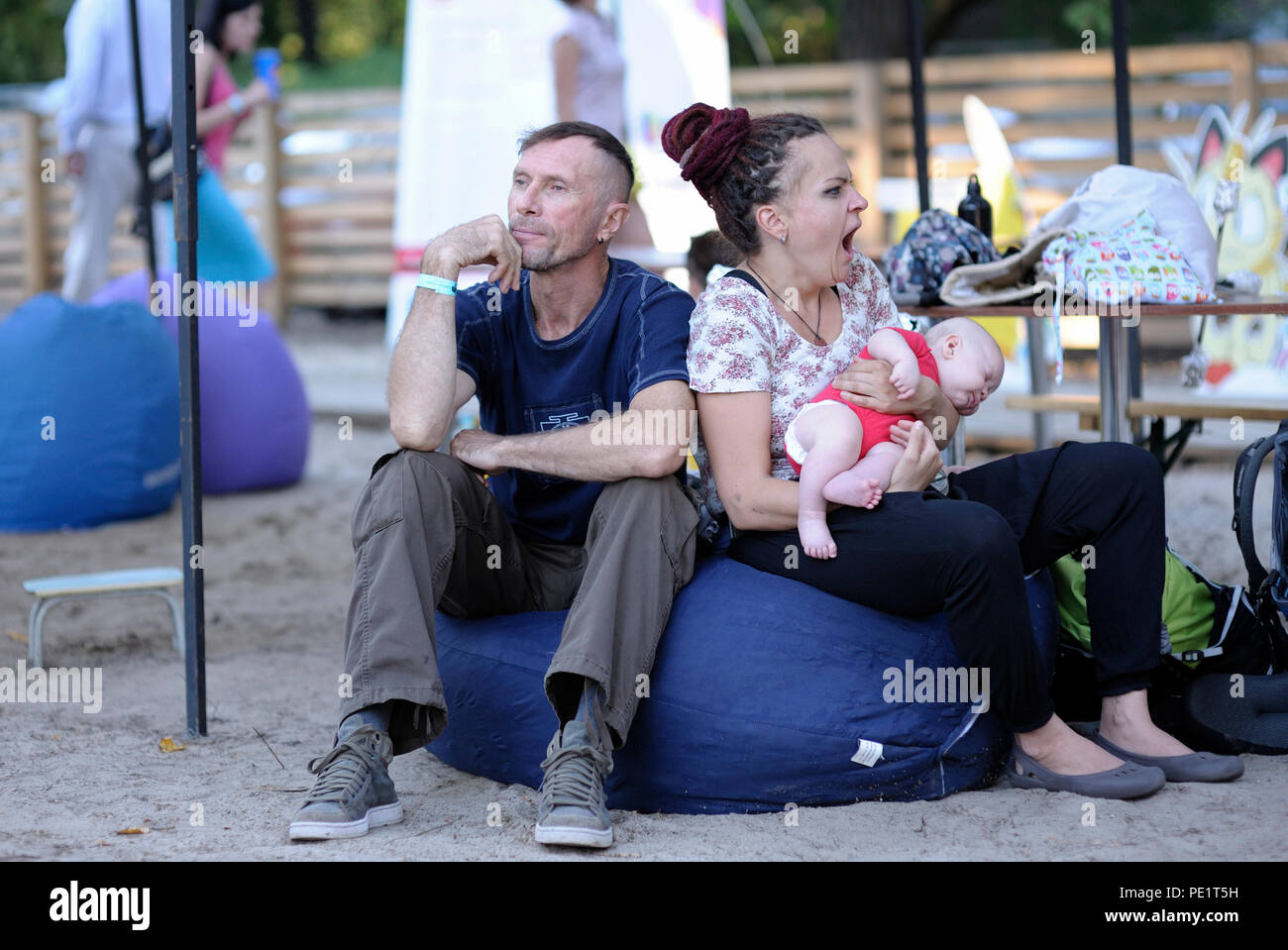 "Man and woman with a baby on hands sitting in bean bag, woman yawning. Fest of Yoga and Vedic Culture ""Vedalife-2018"". July 25, 2018. Kiev, Ukraine Stock Photo"