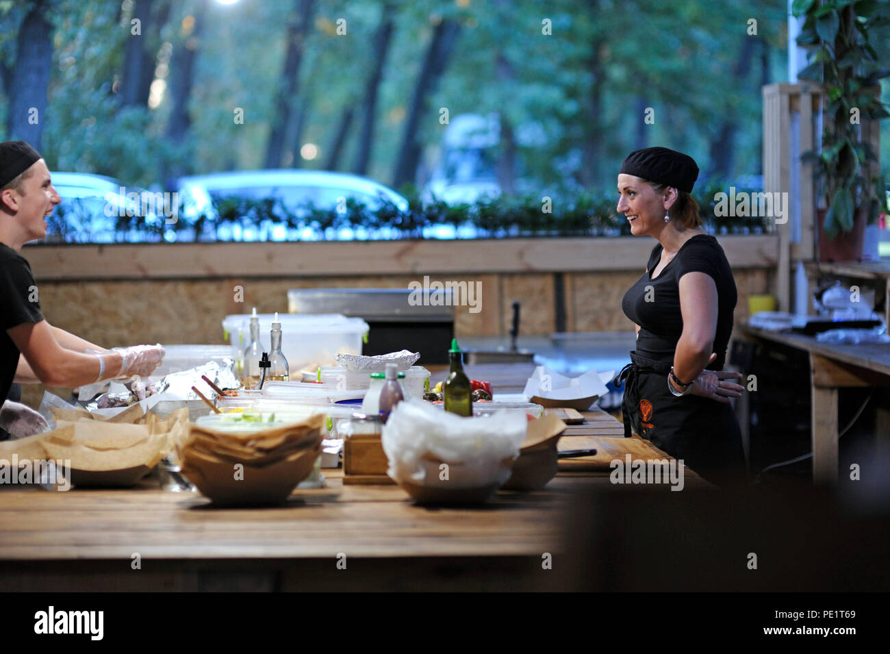 Waiter and waitress communicate while preparing fast food meals on a kitchen table of a restaurant. July 25, 2018. Kiev, Ukraine - Stock Image