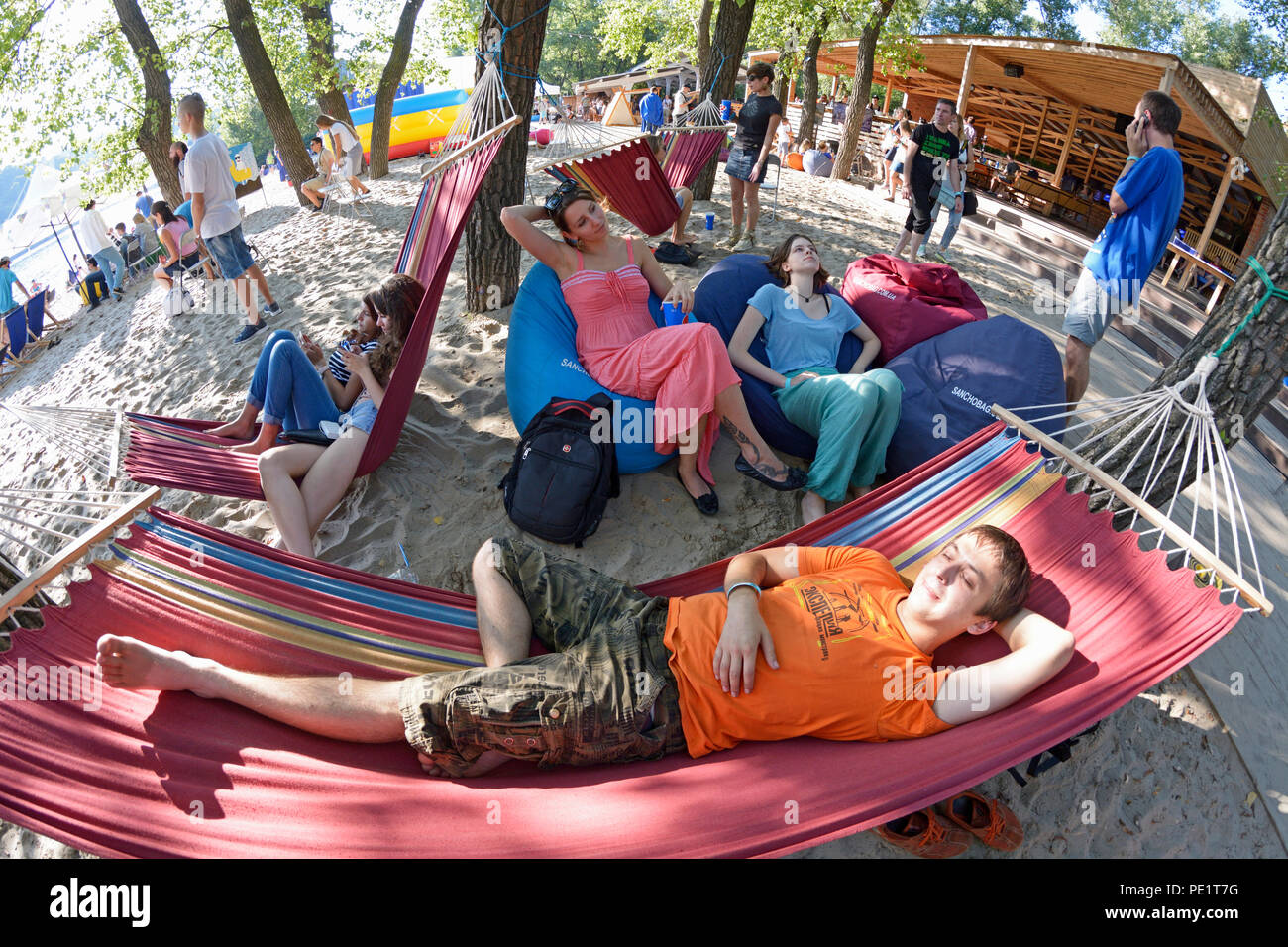 "Man laying in a hammock, women sitting in bean bags. Fest of Yoga and Vedic Culture ""Vedalife-2018"". July 25, 2018. Kiev, Ukraine - Stock Image"