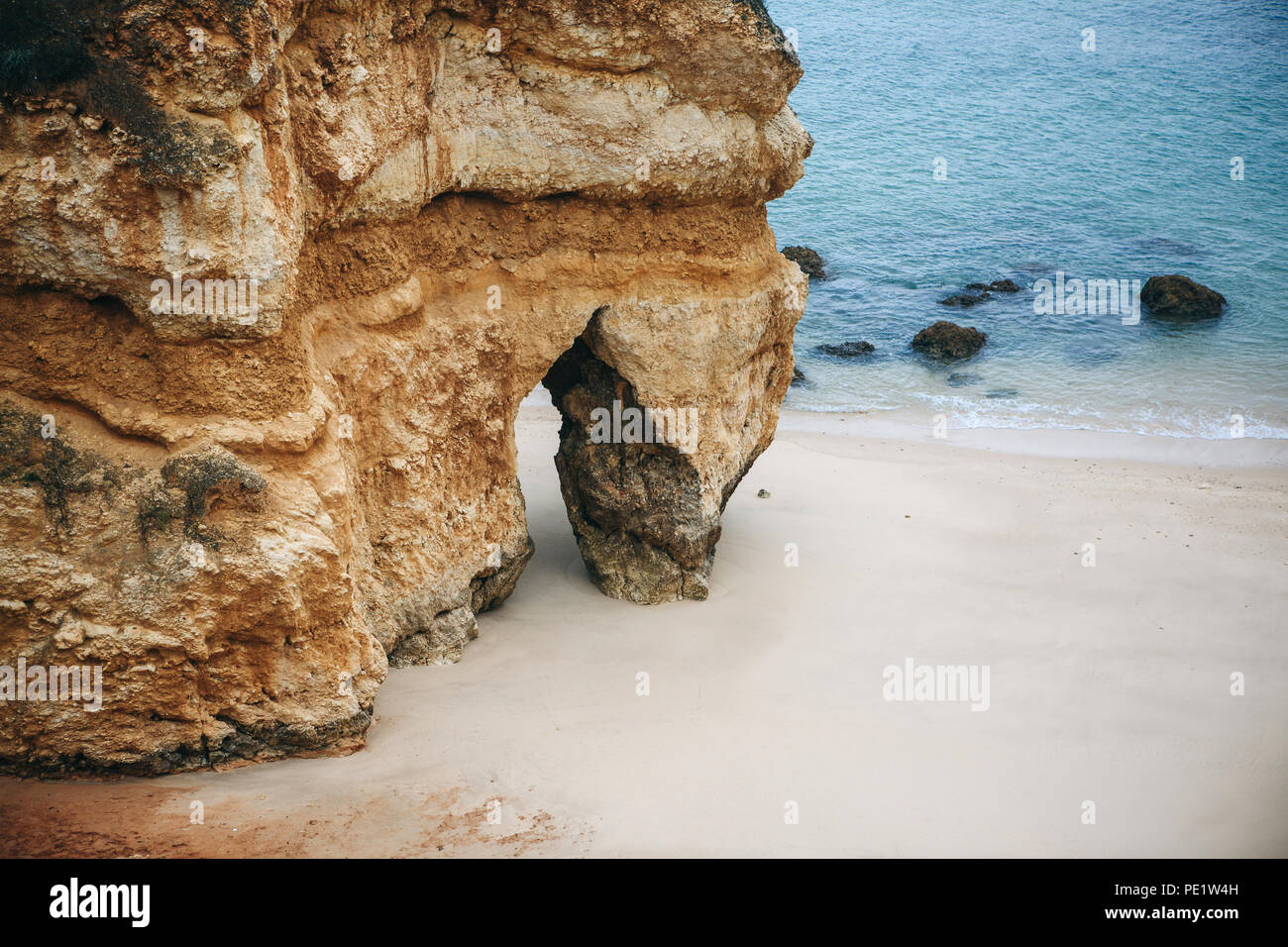 A rock with a crevice on the beach in the city called Lagos in Portugal. Near the Atlantic Ocean. - Stock Image