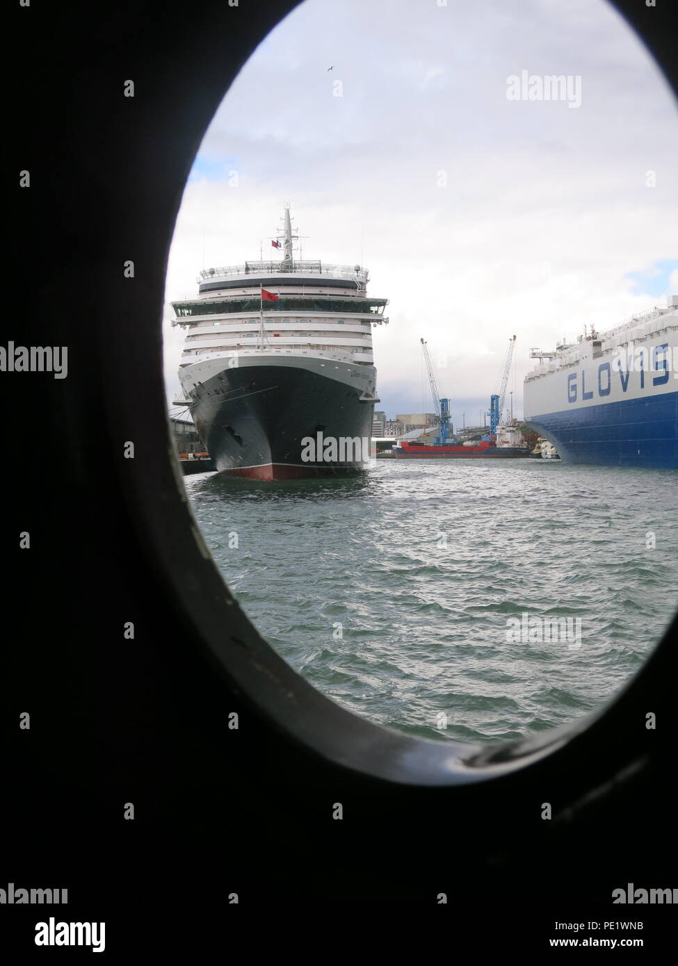A view of the Cunard cruise liner, Queen Victoria, framed by the porthole on the SS Shieldhall, Britain's largest working steamship. Stock Photo