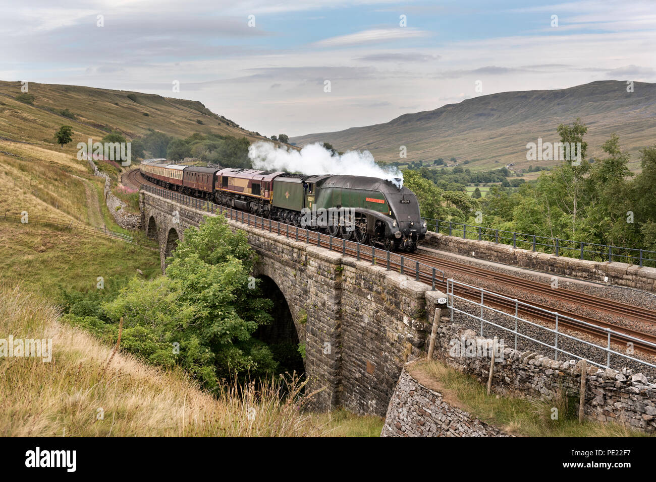 Cumbria, UK, 11 Aug 2018. Steam loco 'Union of South Africa' hauls the Settle and Carlisle Golden Express, Ais Gill Viaduct near the summit of the Settle to Carlisle railway line. Due to fire risk as a result of the dry weather the steam locomotive has to be assisted by a diesel, seen here behind the steam loco. Union of South Africa is an A4 locomotive of the same class as the Mallard, which holds the world steam speed record. 11th August marks the 50th anniversary of the last steam passenger train on British Railways in 1968 and this is celebrated today. Credit: John Bentley /Alamy Live News - Stock Image