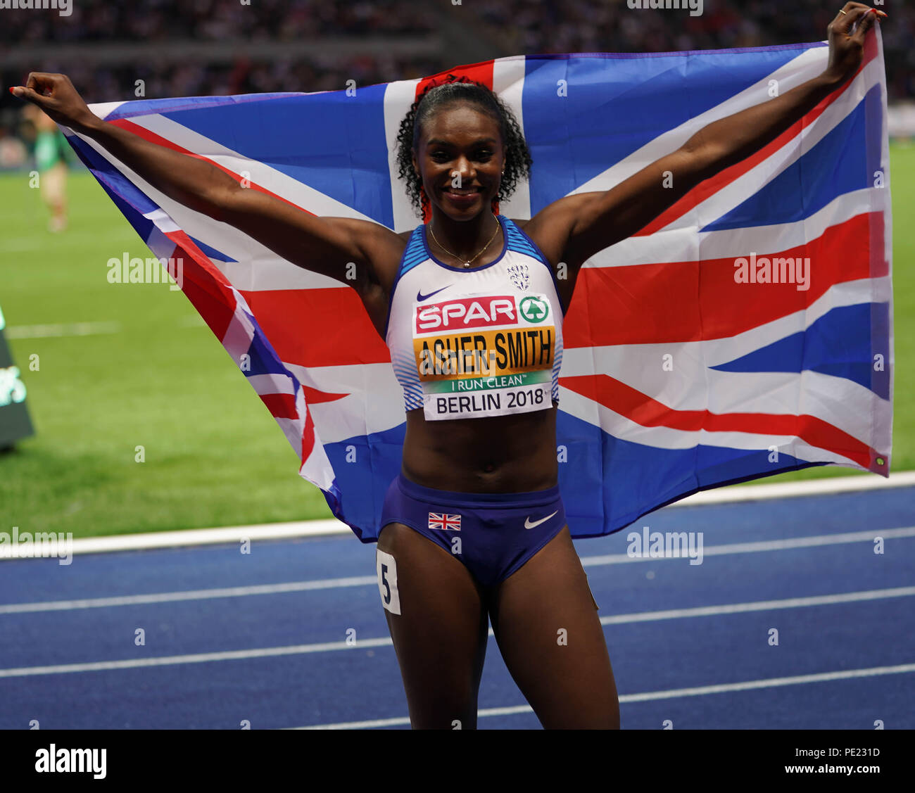 Berlin, Germany, 11 Aug 2018. Dina Asher-Smith (gold) celebrates with the British flag after the Women's 200m on Day 5 of the European Athletics Championships in Berlin, Germany Credit: Ben Booth/Alamy Live News - Stock Image