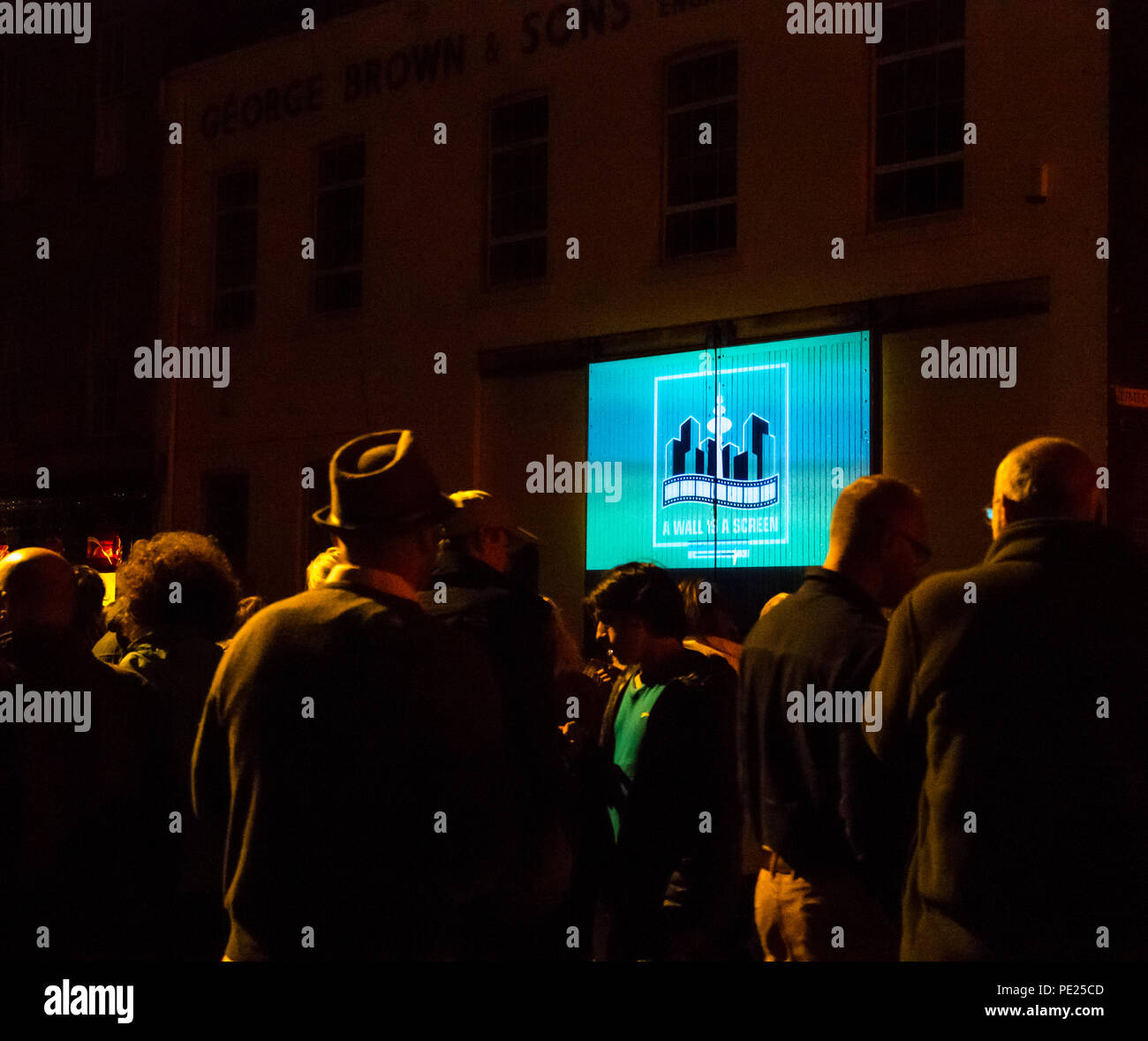 Leith, Scotland, UK. 11th August 2018. Edinburgh Fringe Festival outdoor event A Wall is a Screen: Free guided short film walk with site-specific outdoor screenings on walls of buildings in a tour of five locations in the back streets of Leith, produced by a Hamburg-based short film collective. 600 people attended the event - Stock Image