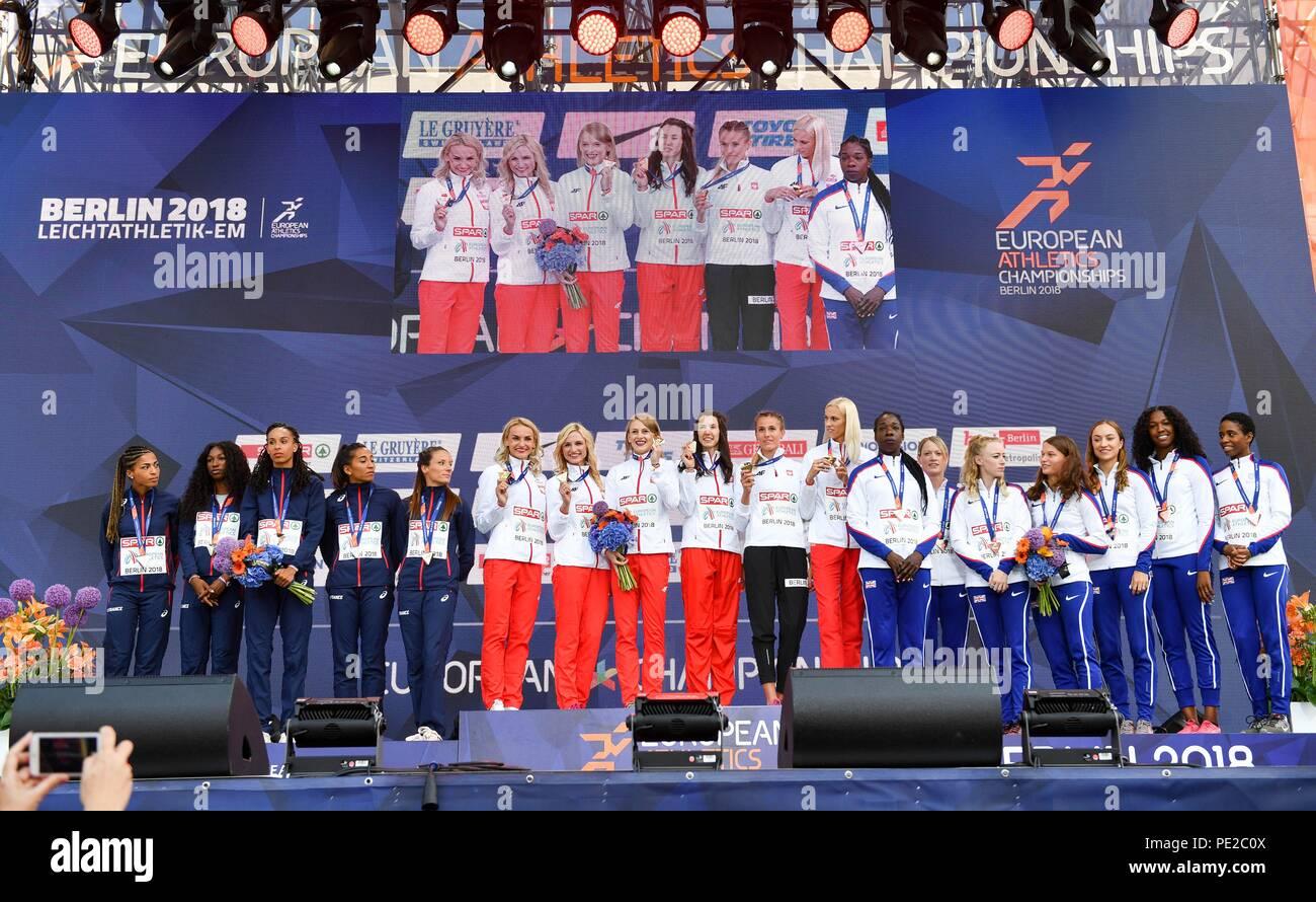 12 August 2018, Germany, Berlin: Athletics, European Championship, award ceremony on the European Mile at Breitscheidplatz, 4 x 400 meters, women. Gold medallists from Poland (M), (Malgorzata Holub, Natalia Kaczmarek, Martyna Dabrowska, Iga Baumgart, Patrycja Wyciszkiewicz, Justyna Swiety), silver medallists from France (l) (Elea Mariama Diarra, Estelle Perrossier, Deborah Sananes, Agnès Raharolahy, Floria Guei) and bronze medal winners from Great Britain (Zoey Clark, Finette Agyapong, Mary Abichi, Emily Diamond, Anyika Onuora, Amy Allcock, Eilidh Doyle). Photo: Bernd Thissen/dpa - Stock Image