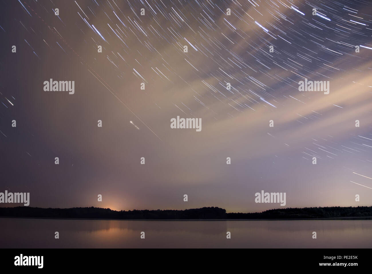 Amazing night landscape with a forest reflected in the smooth water of the river, clouds and stars in the form of tracks on a dark blue sky Stock Photo