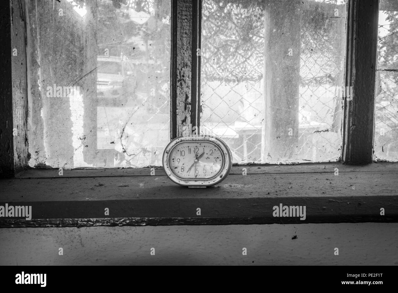 Old clock on the window of an abandoned house - Stock Image