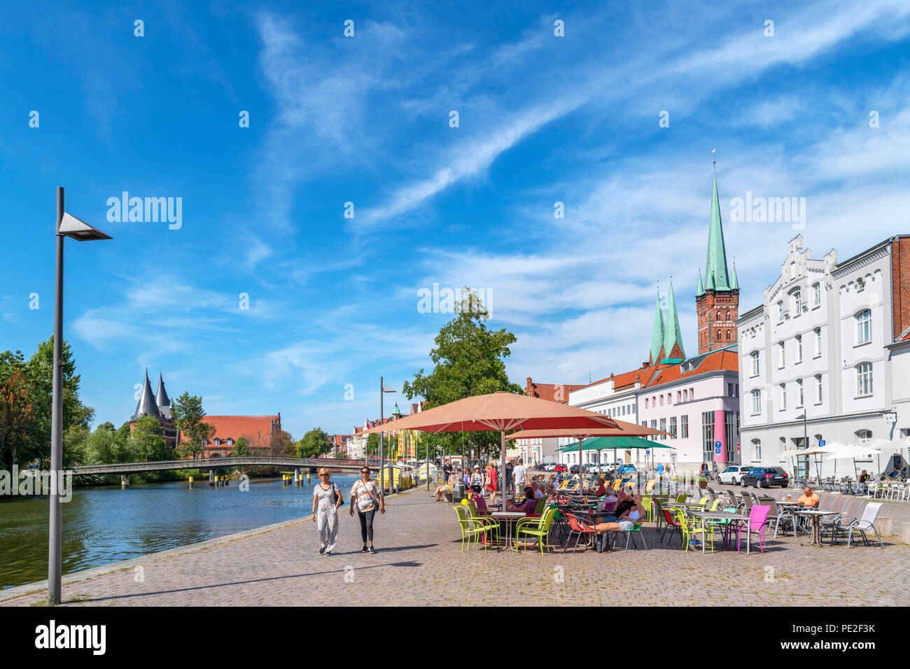 Sidewalk cafe on the banks of the River Trave, Lubeck, Schleswig-Holstein, Germany - Stock Image