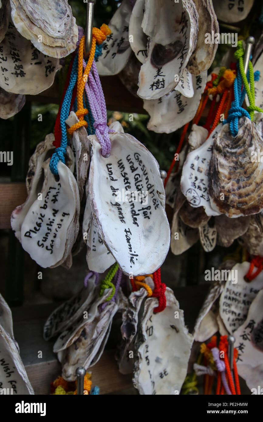 Foreign wishes. Writen wishes on oyster shells (Ema) at Kakigara Inari a Shinto Shrine at the Hase-dera temple in Kamakura, Kanagawa Prefecture, Japan - Stock Image