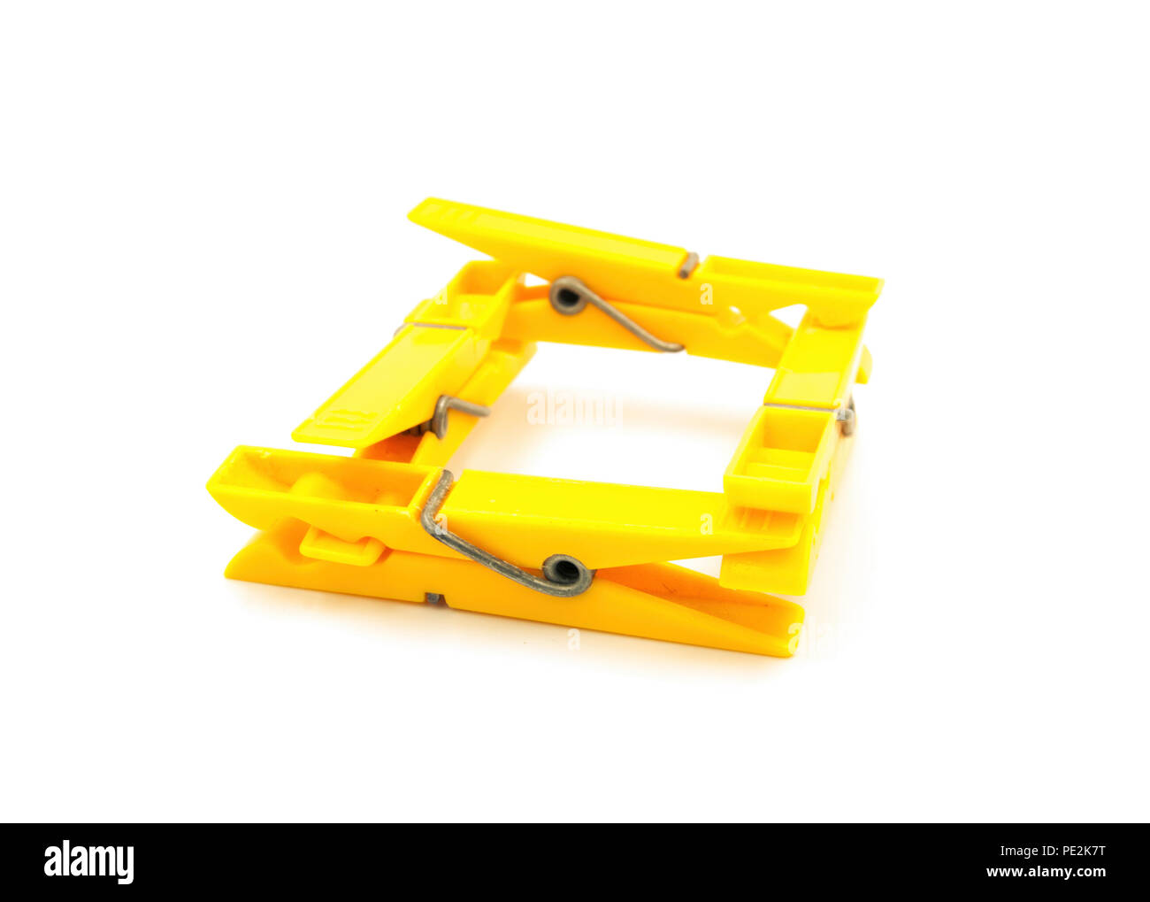 Four yellow pegs on white background - square Stock Photo