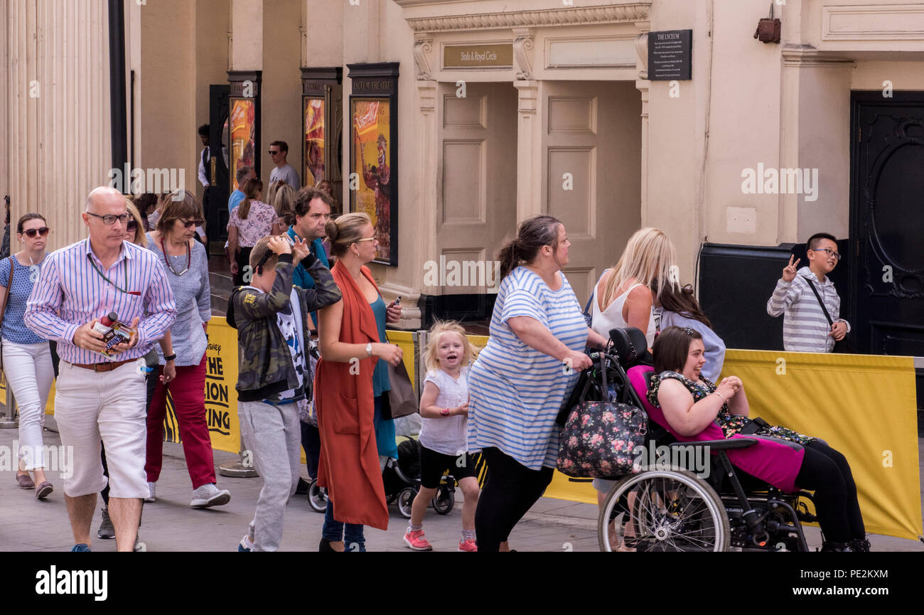 Hustle and bustle of people walking past theatre, young boy behind theatre barrier giving peace sign. London, England, UK - Stock Image