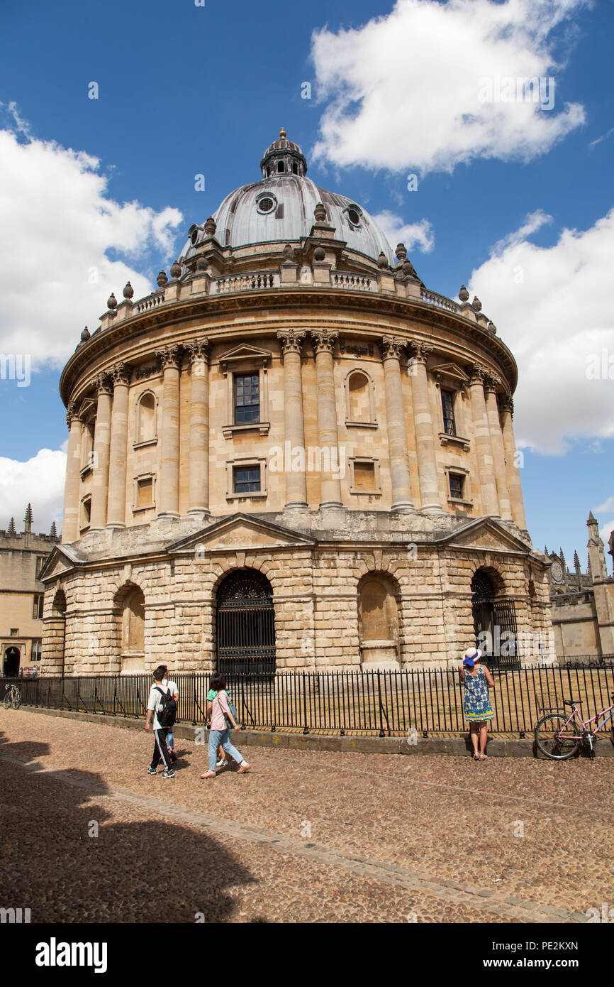 Woman standing looking at the The Radcliffe Camera part of the Bodleian Library situated in Radcliffe square Oxford England UK Stock Photo