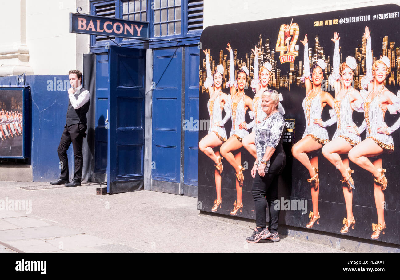 Woman standing in front poster, with female tap dancers, advertising 42nd street, London, England, UK - Stock Image
