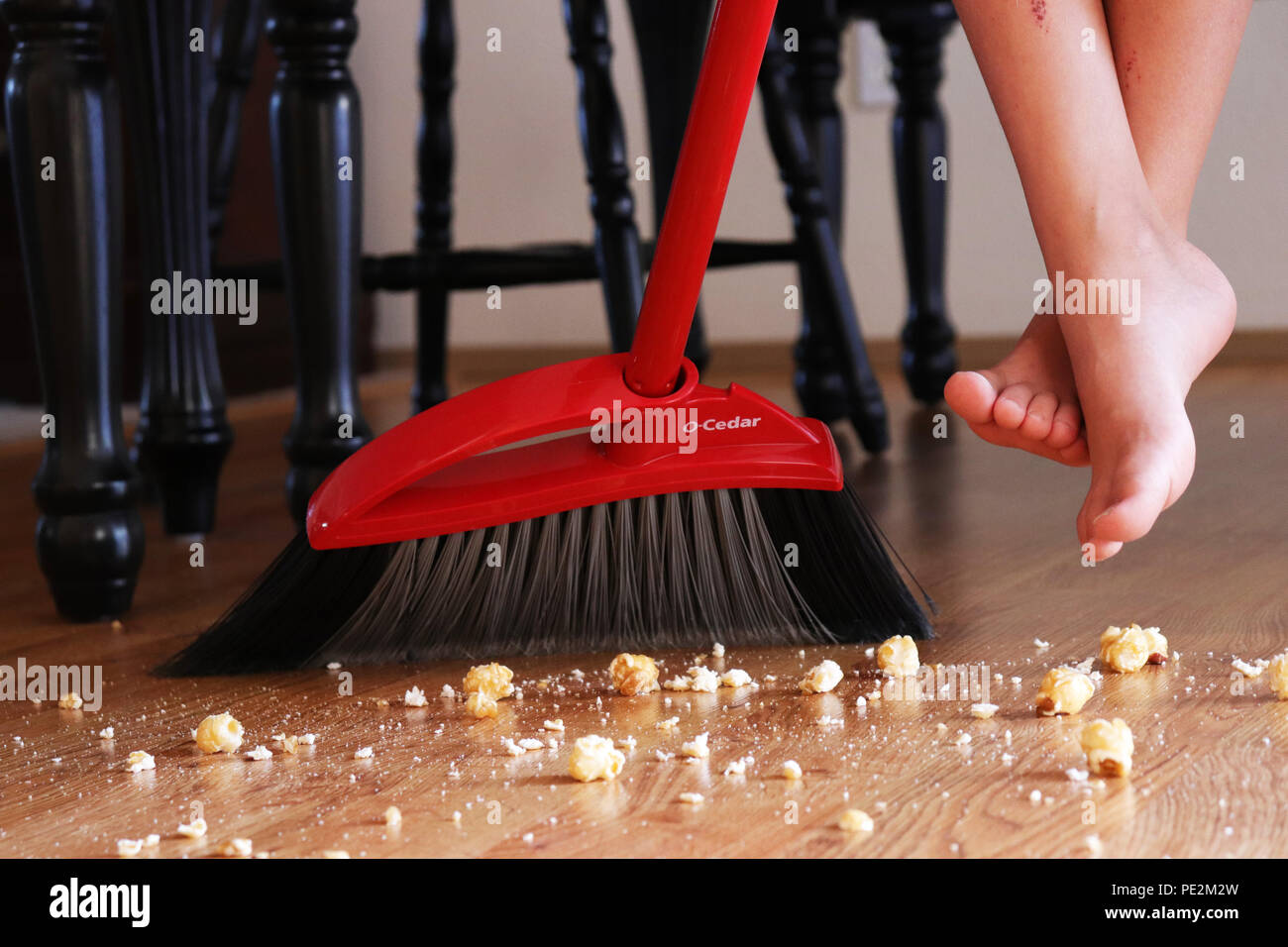 Cleaning up a child's mess with O-Cedar broom - Stock Image