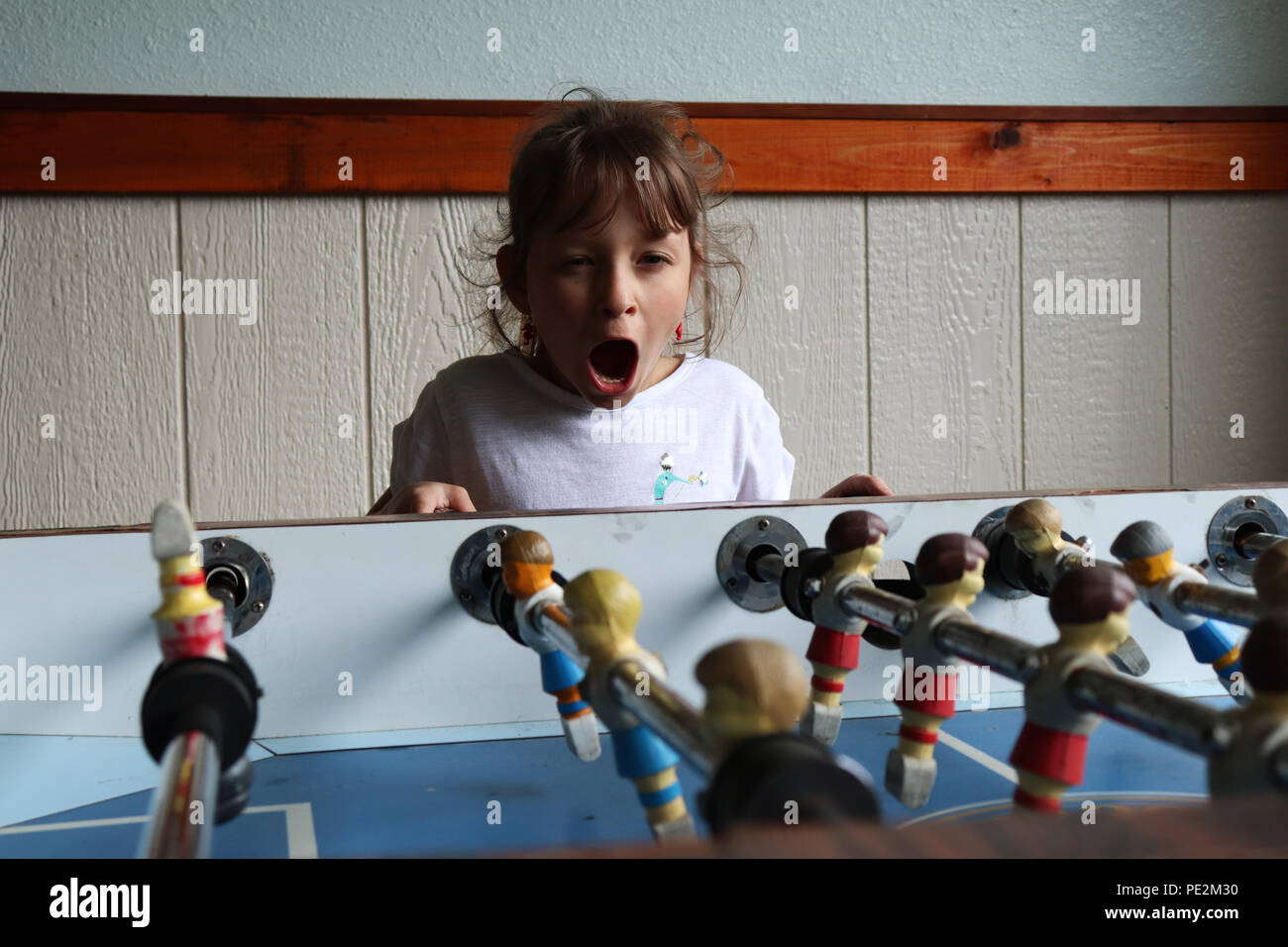 Little girl playing fussball table - Stock Image