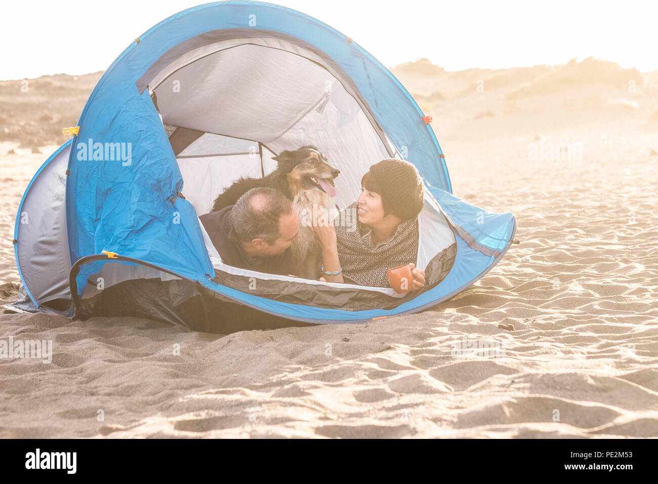 couple in outdoor free camping leisure activity have fun inside tiny home at the beach. Dog border collie behind them with love and friendship forever - Stock Image