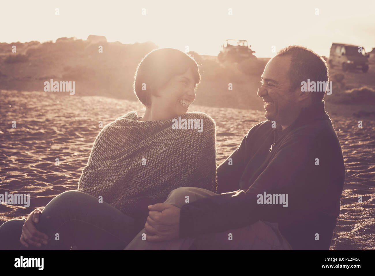 nice beautiful middle age 40 years old couple man and woman caucasian hugged and stay together on the beach sitting in the sand and enjoying a golde a - Stock Image