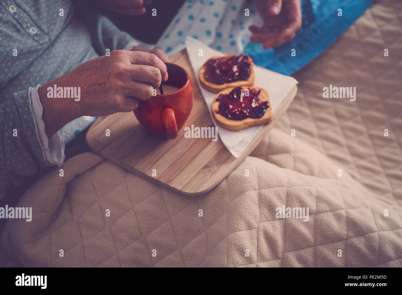 caucasian aged couple doing breakfast at home in the bed. nice natural scene at home for togheterness life concept. love and carefree people married. - Stock Image
