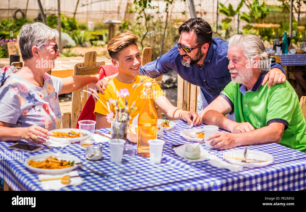 caucasian family in relationship and friendship sitting outdoor in a natural place made with recycled wood. from grandfthers to mother to son. old, mi - Stock Image