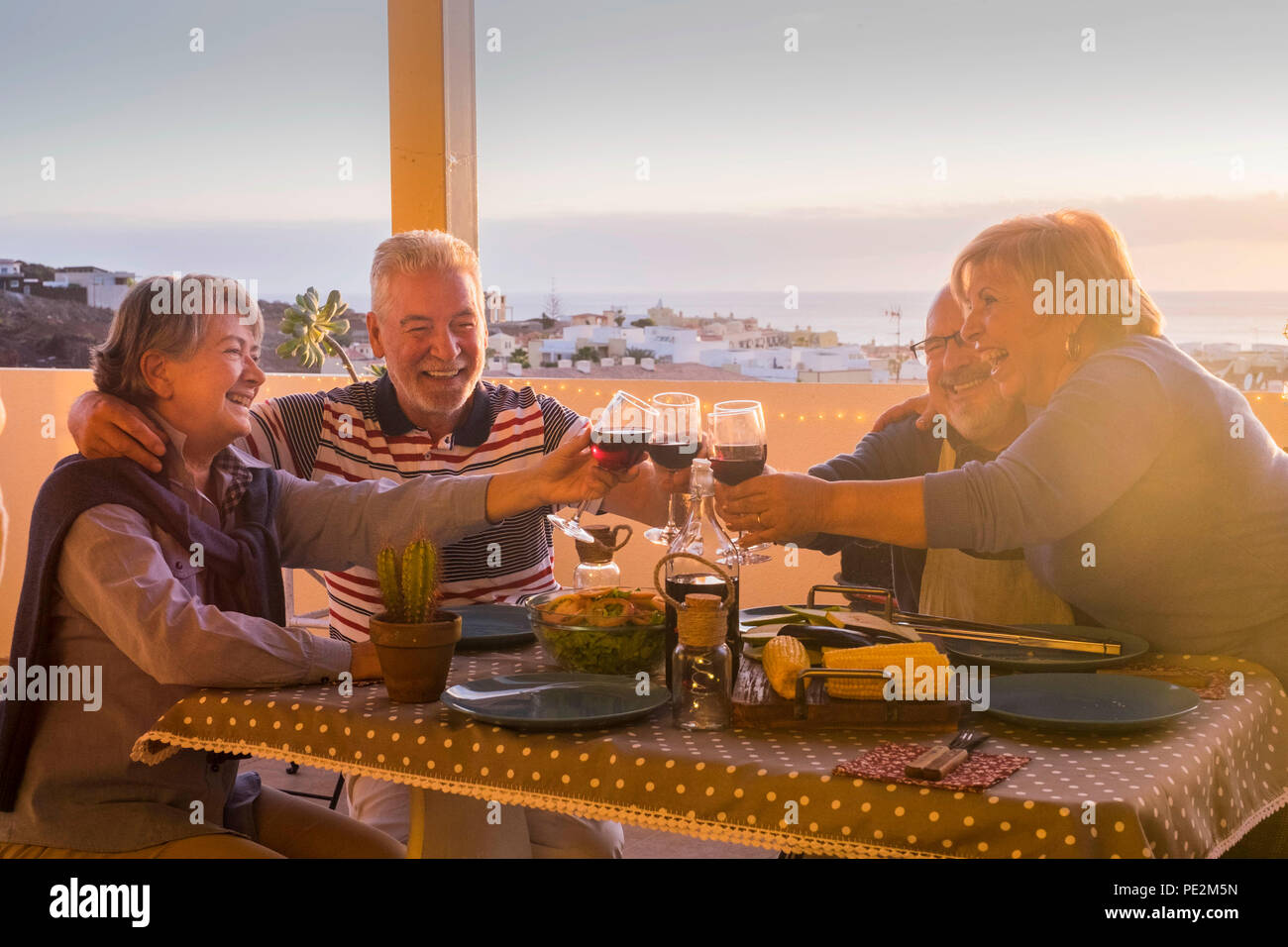 nice group of caucasian adult people in happiness staying together for dinner outdoor in the terrace. love and friendship concept with amazing view. v Stock Photo
