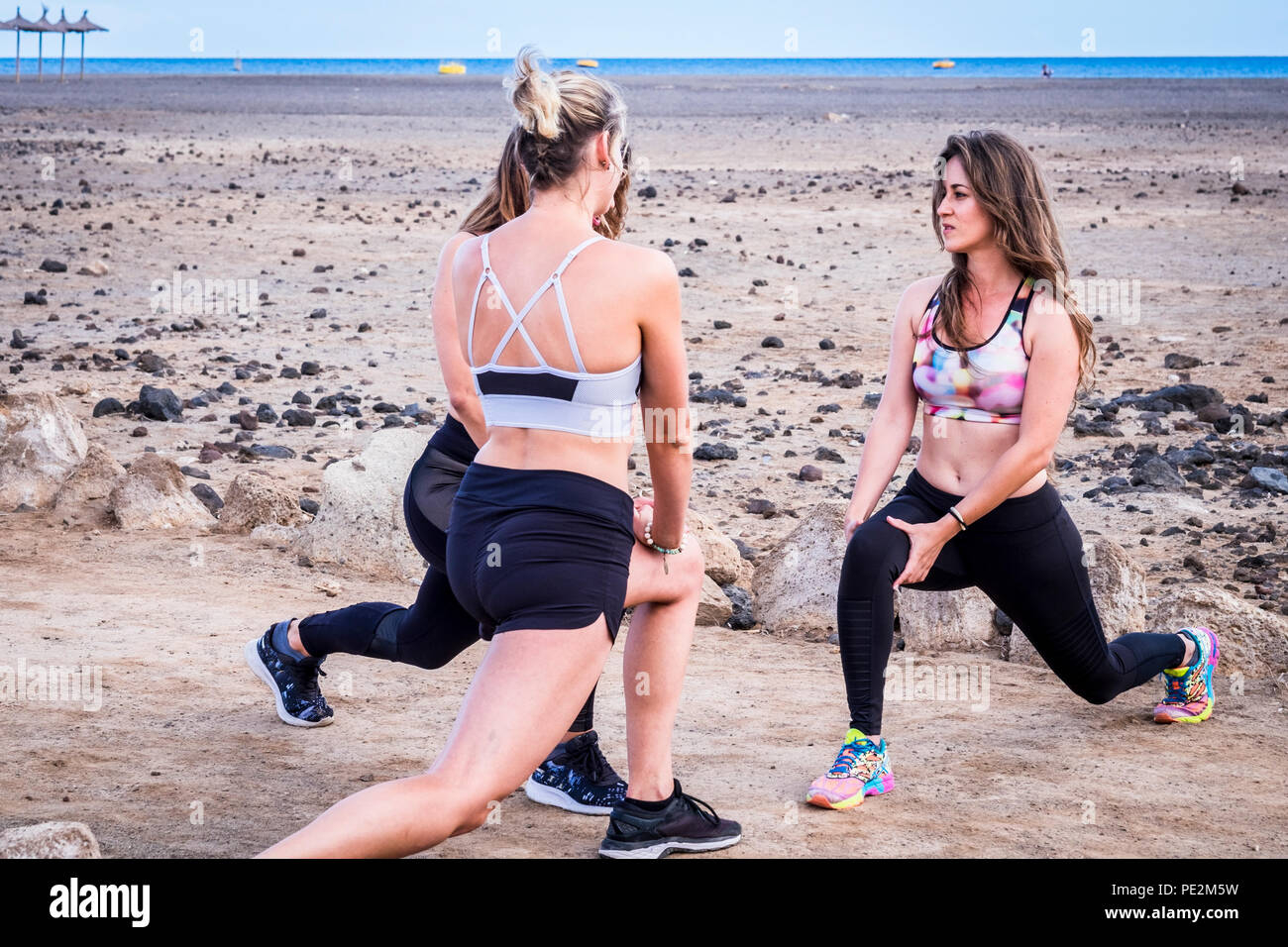 Group Of Three Fit Beautiful Caucasian Babes Yong Woman Do Exercises Outdoor At The Beach Near The Ocean Feeling With The Nature And Love Fitness And