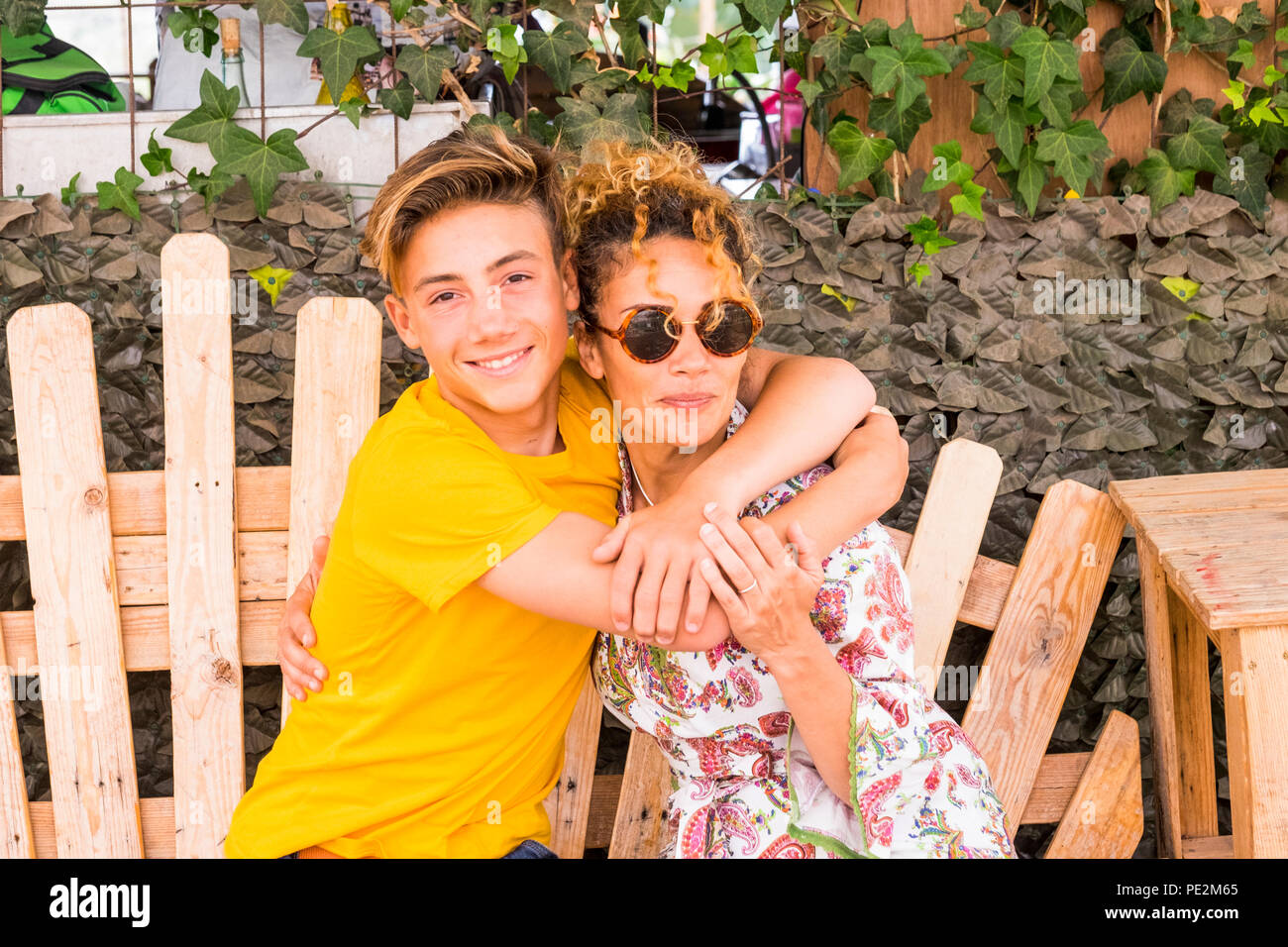 mother and son hugging with smile and enjoy leisure time together with love. family teenager boy 14 years old and mom 43 have fun sitting on a wodd be - Stock Image