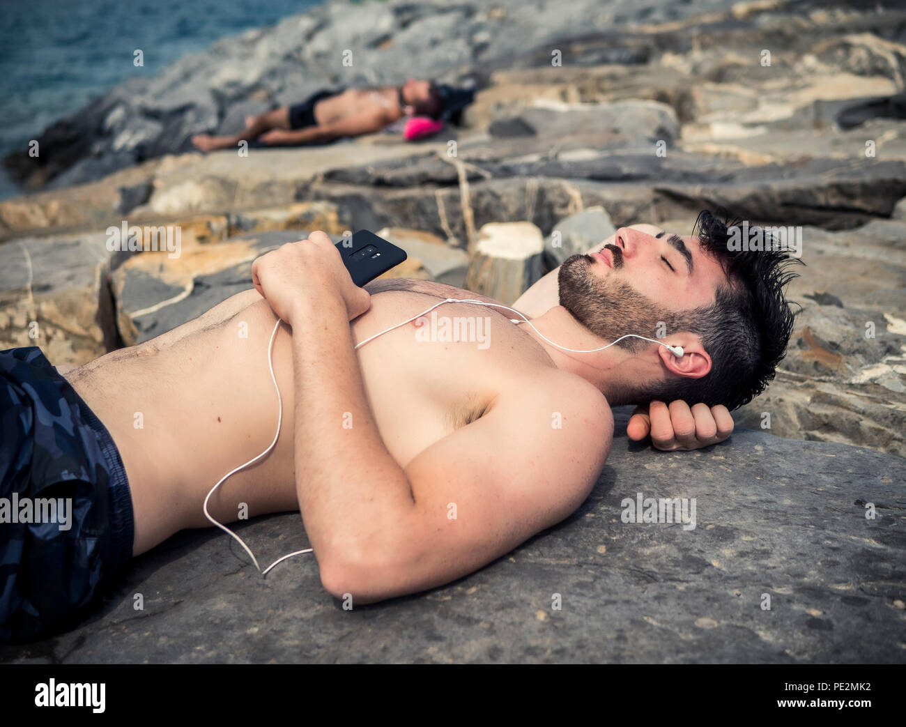 Young man at beach listening to music with earphones Stock Photo