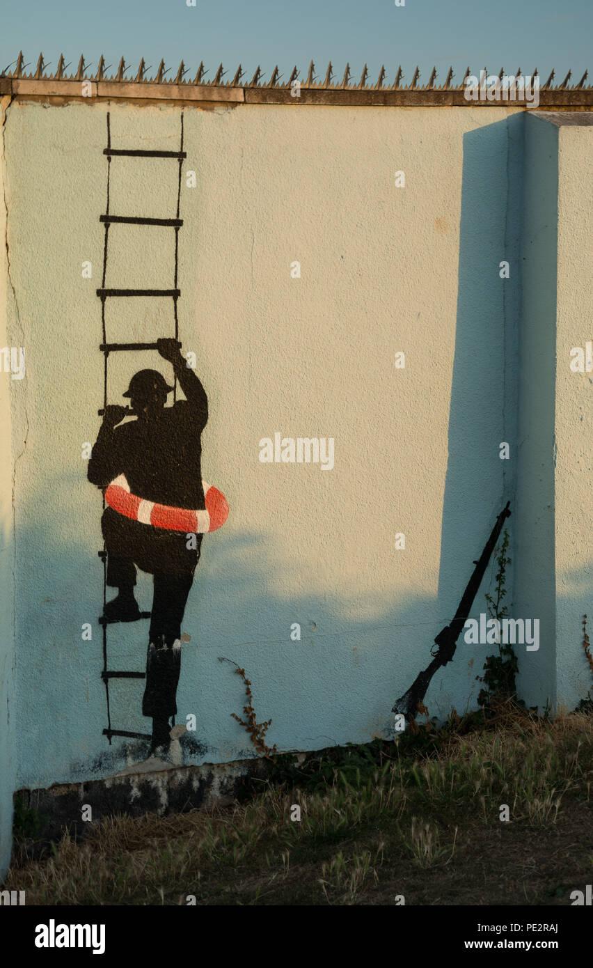 Graffiti of Man climbing rope ladder, street art - Stock Image