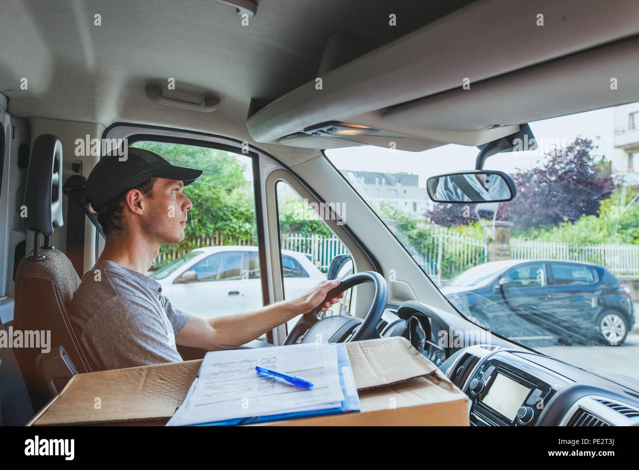 delivery transportation service job, driver man with package box driving truck car vehicle - Stock Image