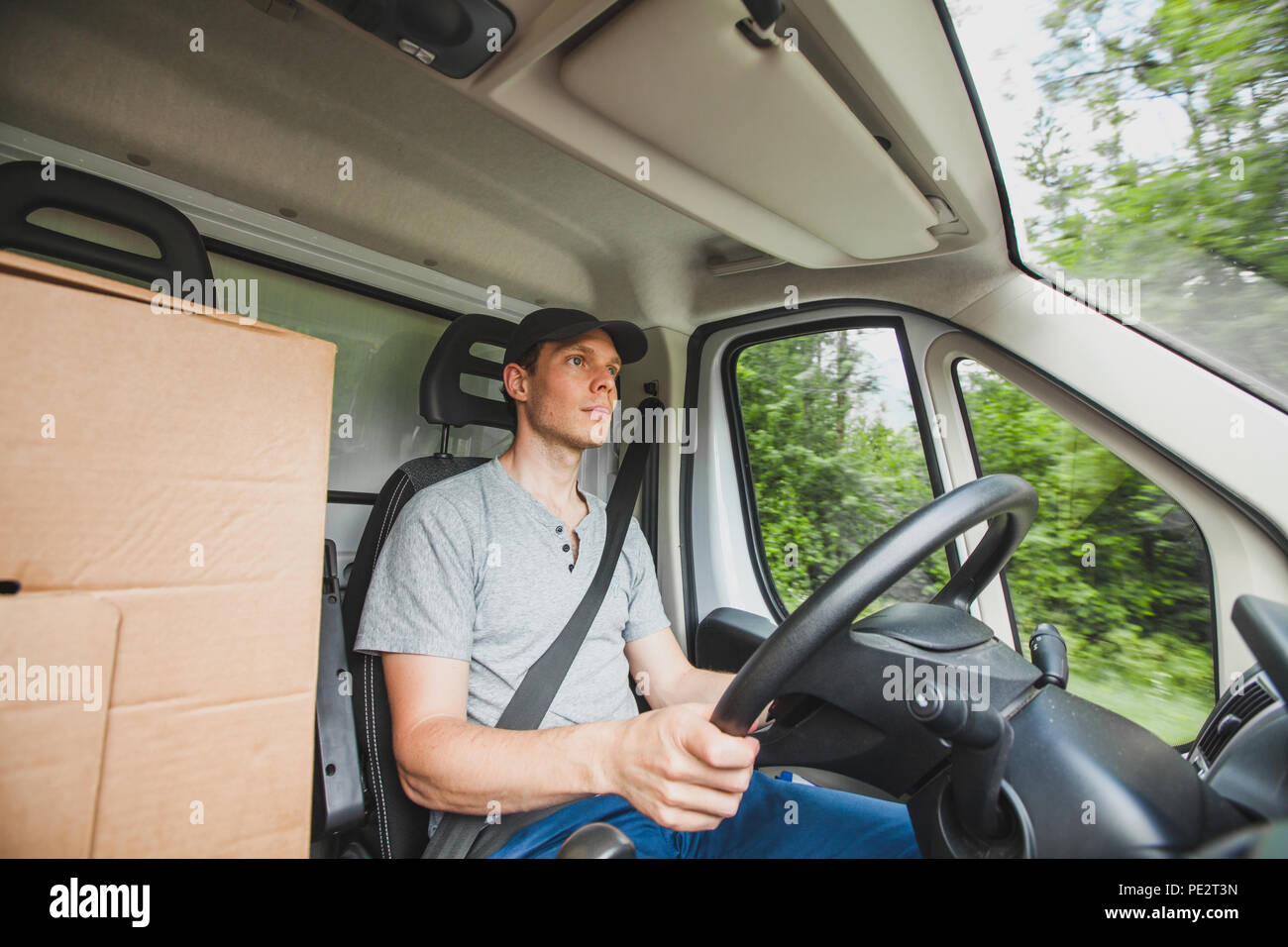 driver man driving delivery truck car vehicle, service of delivering package cargo, transportation occupation job - Stock Image
