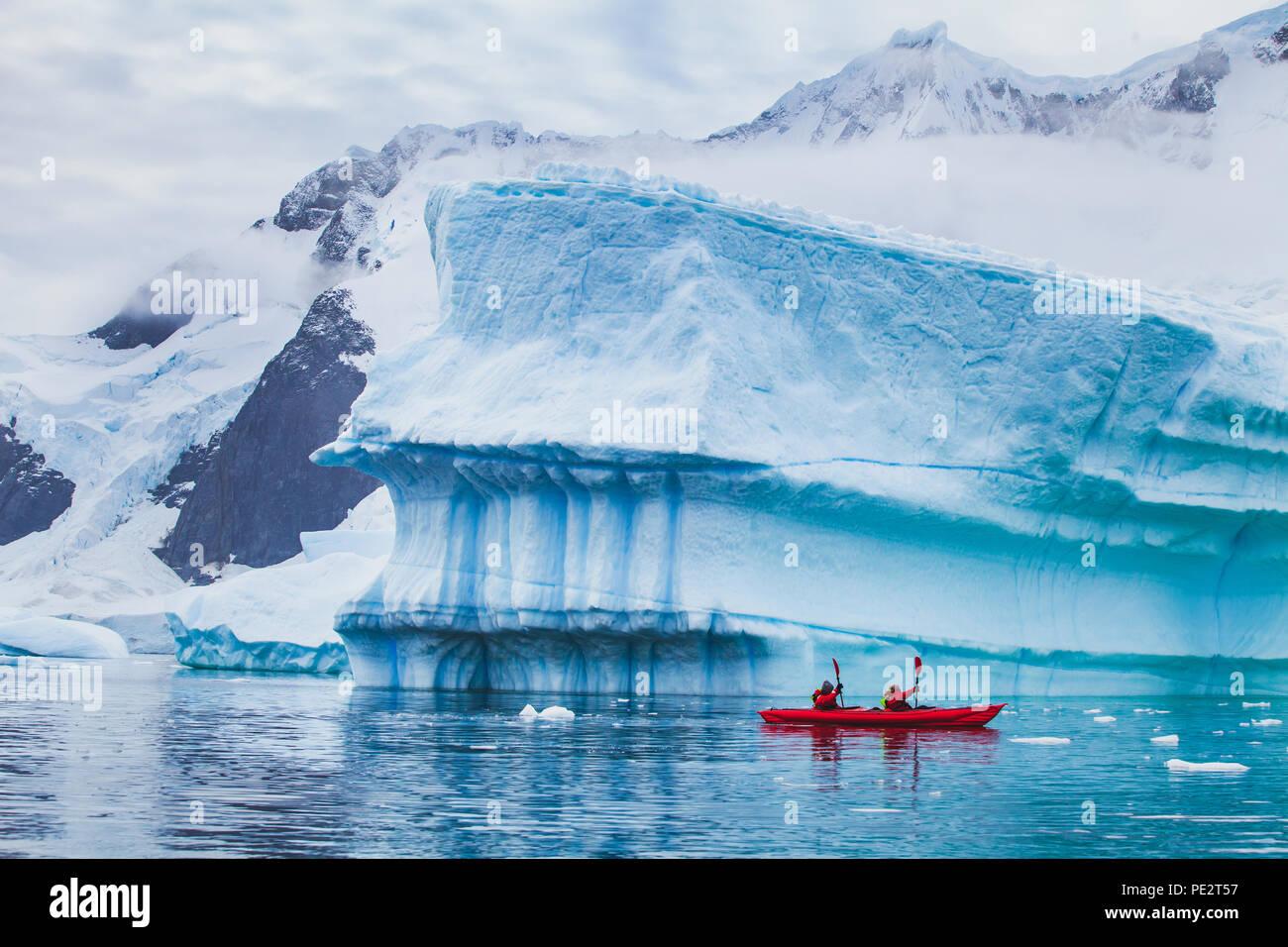 winter kayaking in Antarctica, extreme sport adventure, people paddling on kayak near iceberg Stock Photo