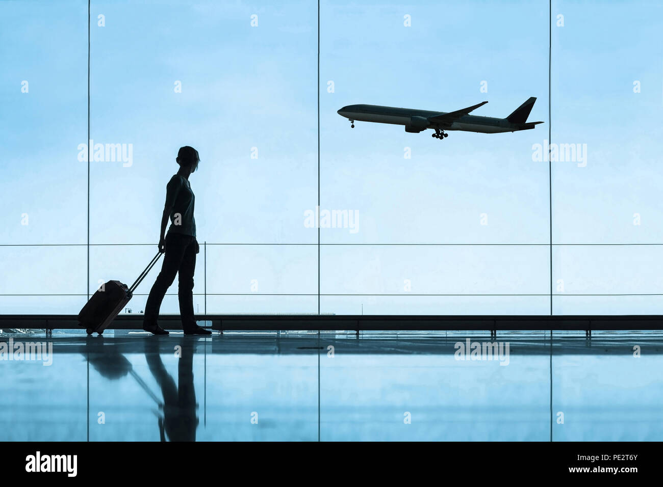 silhouette of woman in airport traveling with luggage suitcase, travel and tourism concept, airplane tickets Stock Photo