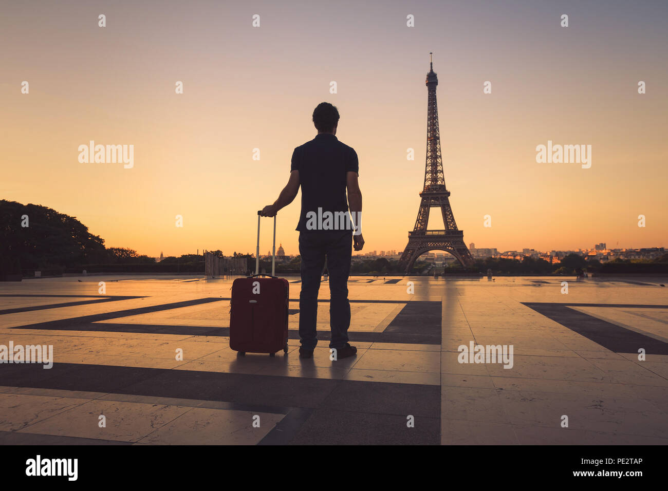 tourist in Paris looking at Eiffel Tower, silhouette of man with luggage travel to France Stock Photo