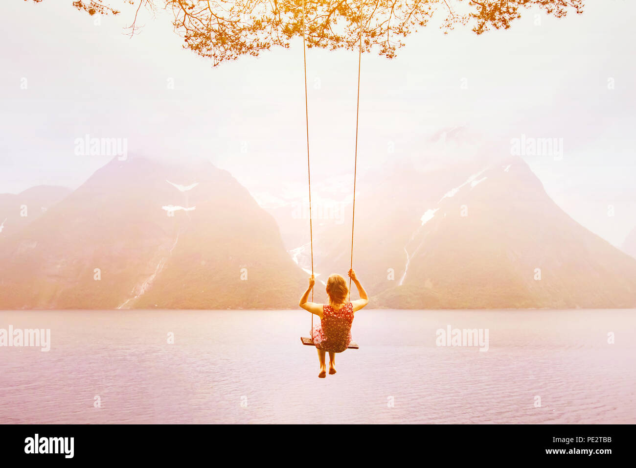 inspiration, travel and daydream concept, beautiful young woman romantic dreamer on the swing in amazing summer inspirational landscape background - Stock Image