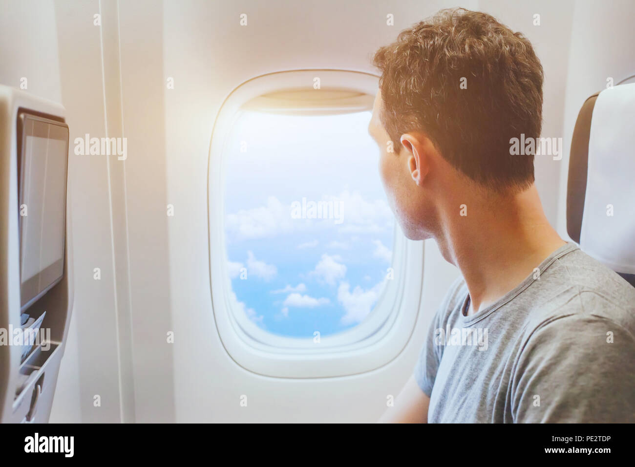 passenger of airplane looking at window, international travel, happy man tourist enjoy flight in comfortable air plane - Stock Image