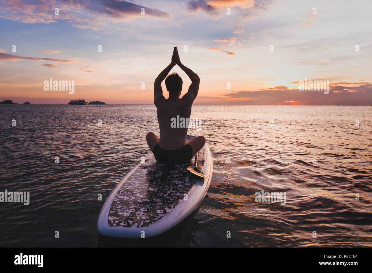 yoga on SUP, silhouette of man sitting in lotus position on stand up paddle board Stock Photo