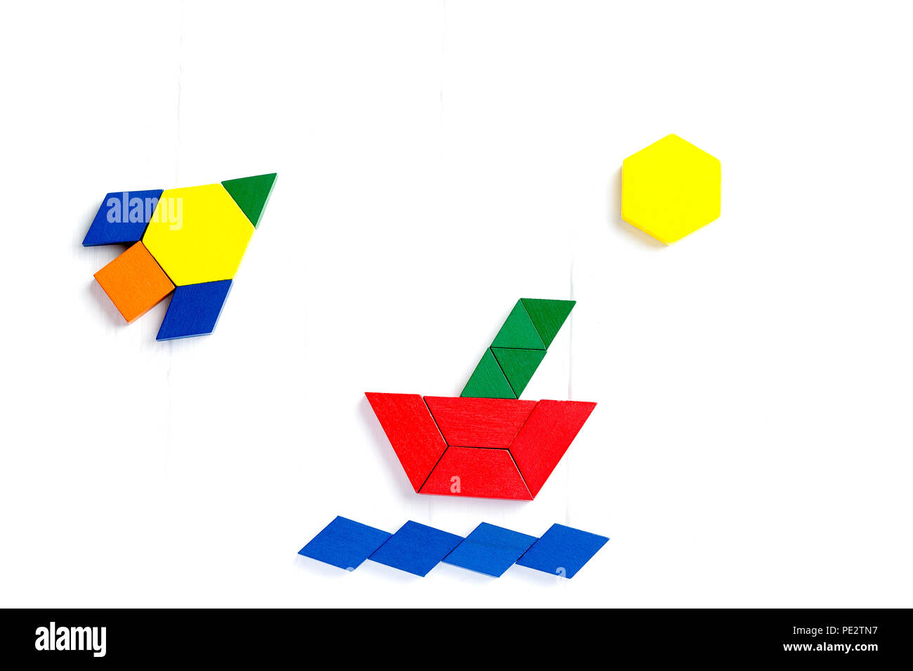 The ship sails on the sea waves, the sun shines brightly. Summer happy atmosphere. A child plays with colored blocks constructs a model on a light woo - Stock Image