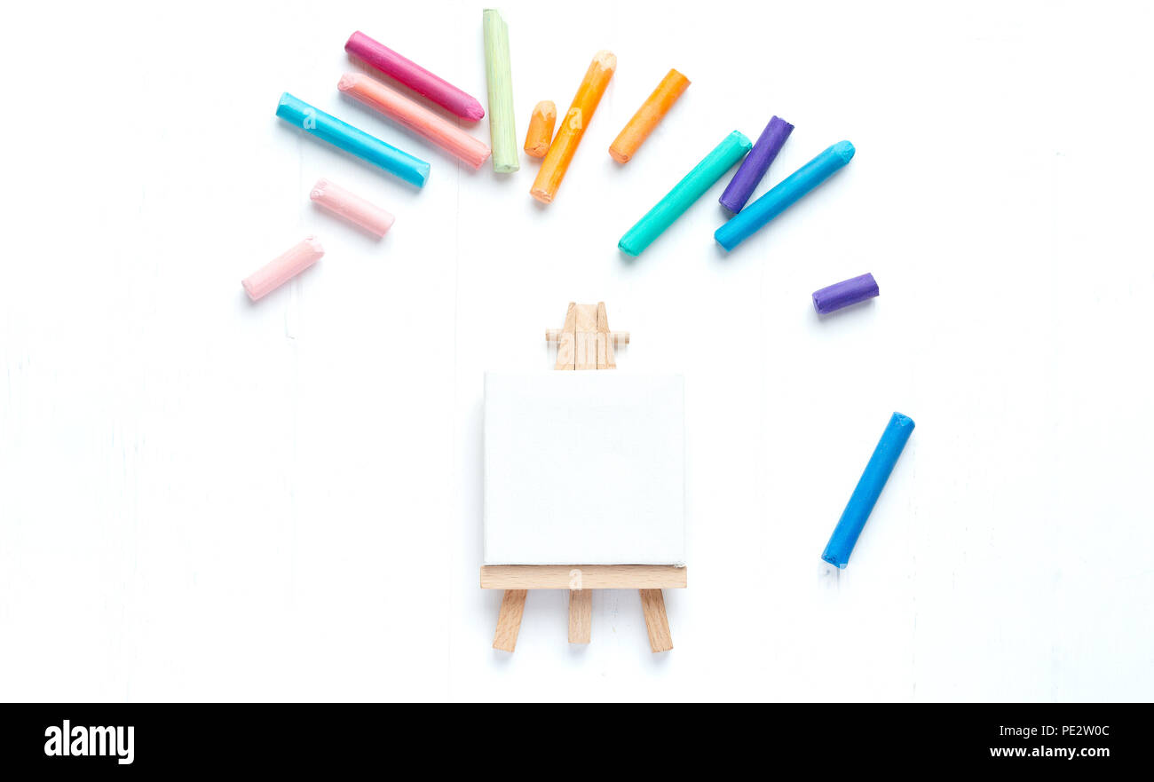 A small malbert with a clean canvas on a white background surrounded by colorful crayons. Template - Stock Image