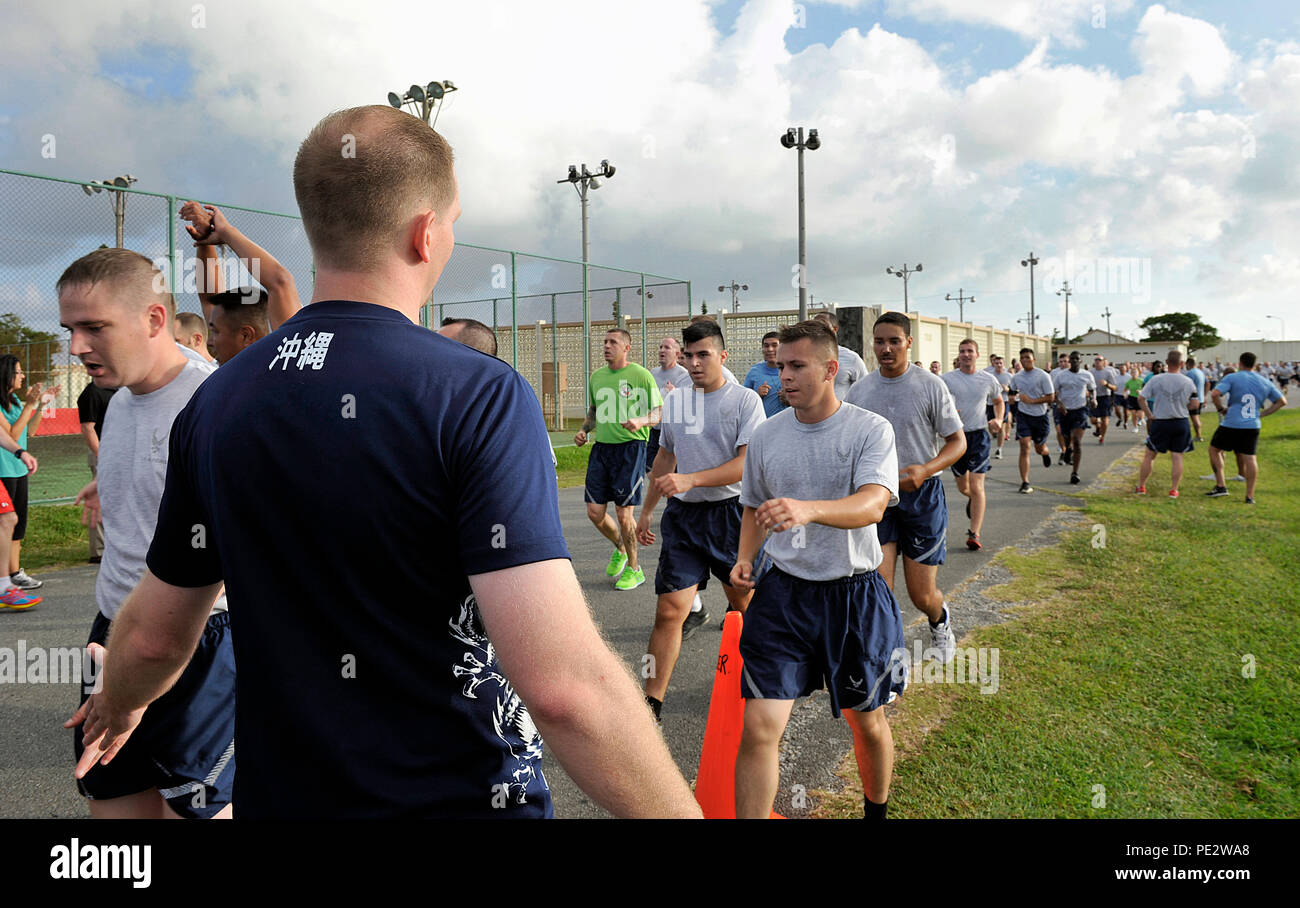 Kevin Ball, 18th Force Support Squadron Risner Fitness Center director, welcomes runners at the finish line Sept. 25, 2015, on Kadena Air Base, Japan. The event was coordinated as part of national suicide prevention awareness month to increase awareness of suicide prevention resources. (U.S. Air Force photo by Naoto Anazawa) - Stock Image